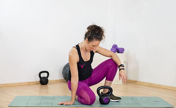 photo of woman with kettlebells